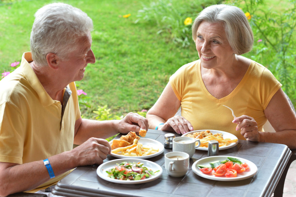 A senior man and woman are eating a healthy meal together outside.