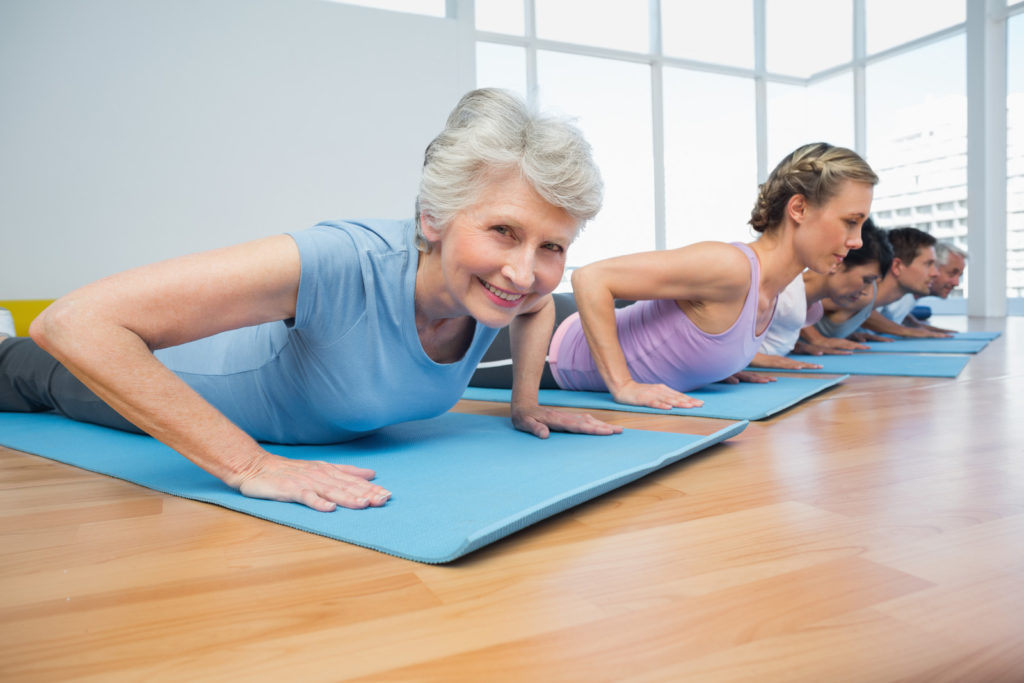 A senior woman is lying on an exercise mat doing yoga poses.