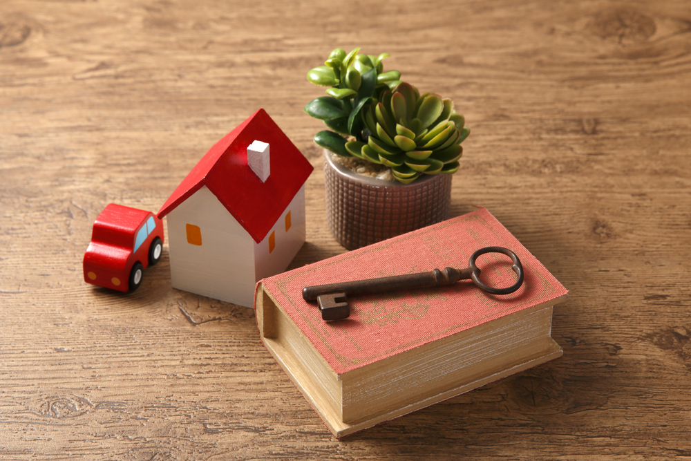 skeleton key sitting on book with toy house and car