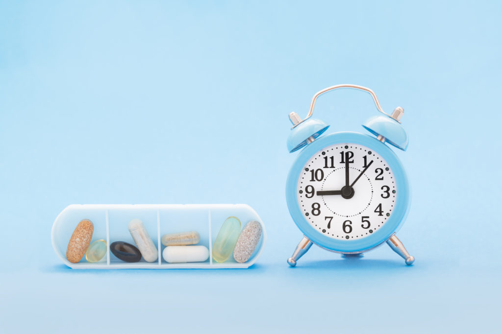 small pill box and blue clock on pastel blue background