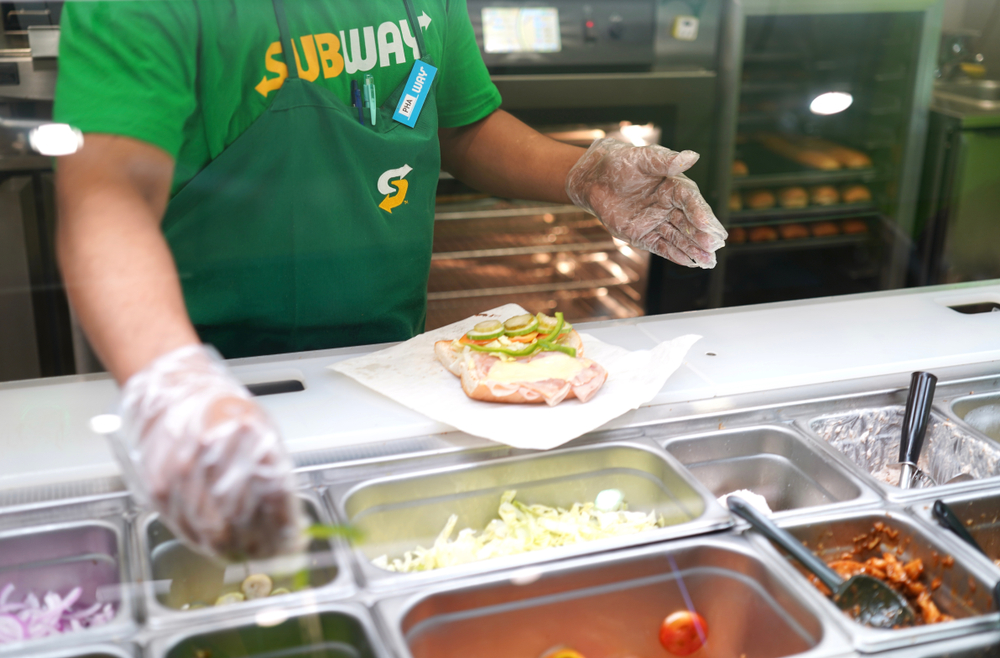 subway worker making a fresh sub with a la carte ingredients