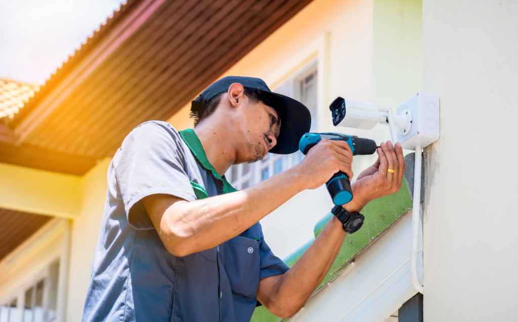 technician installing an outdoor security system