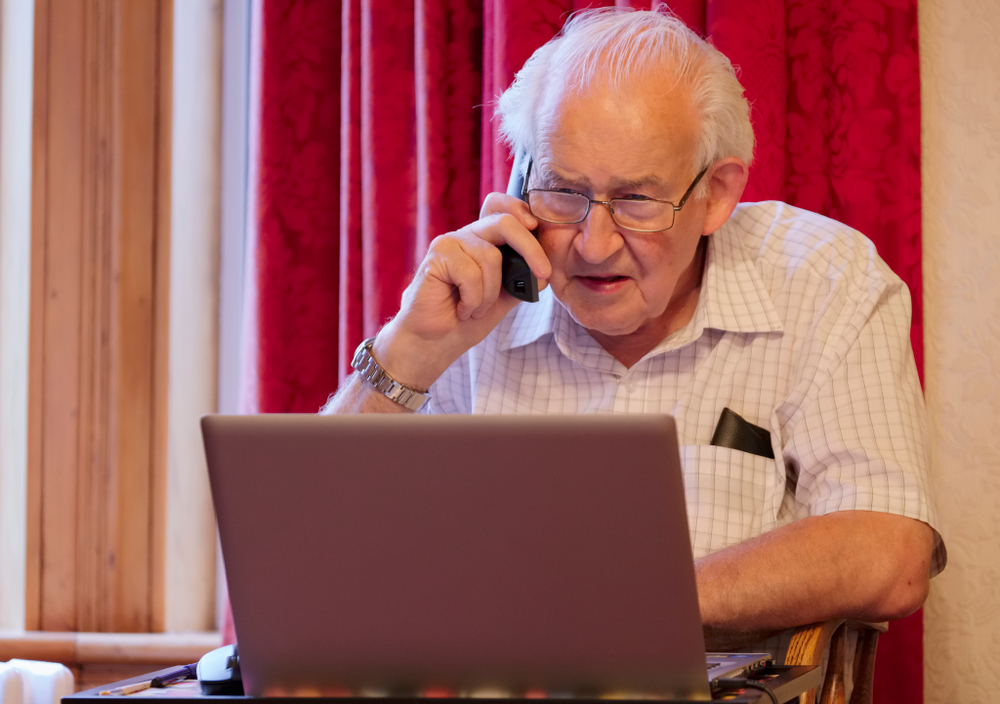 senior man on the phone looking confused while looking at computer screen