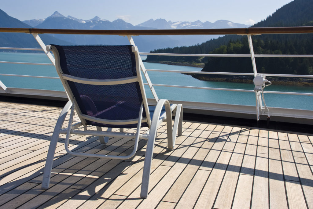 A deck chair sits on the deck of a ship with the mountains and ocean of Alaska in the background.