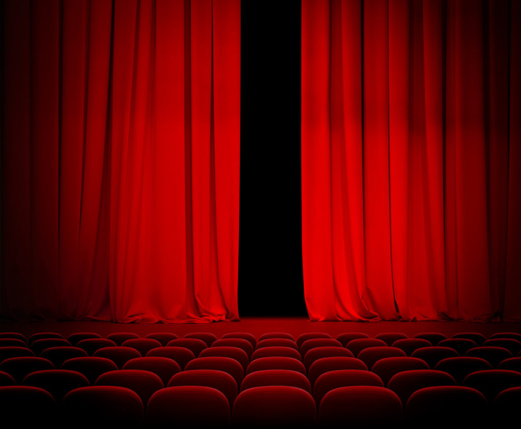 A theatre with red seats in front of a stage with an open stage curtain.