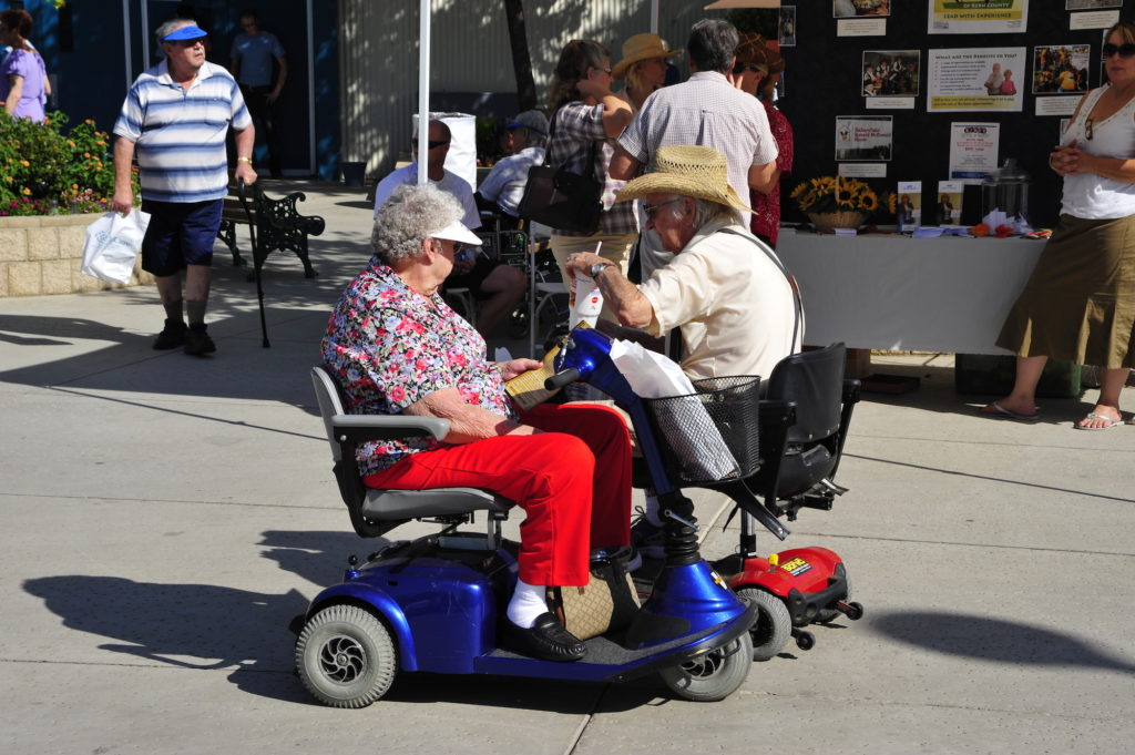 two elderly people in mobility scooters talking at a fair