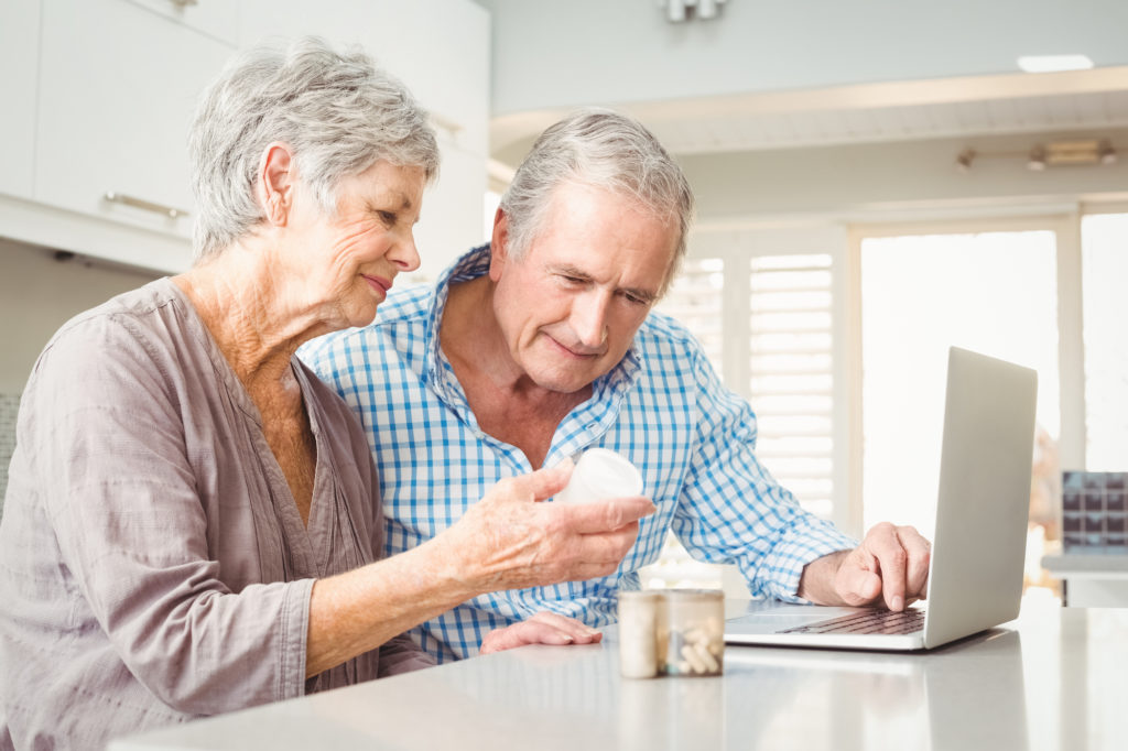 two senior citizens looking at a pill bottle with confused look and looking up information on a laptop