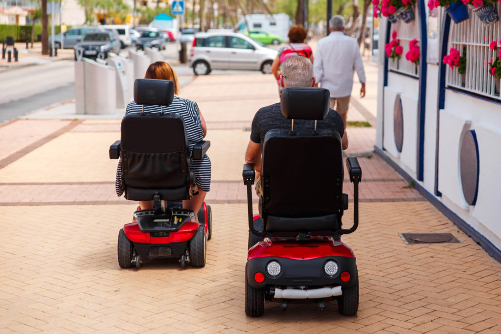 two senior citizens riding mobility scooters in downtown