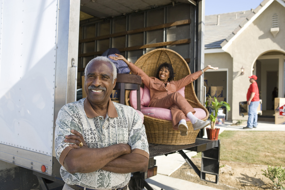 two seniors in front of moving truck with senior woman sitting in modern chair and movers in the background