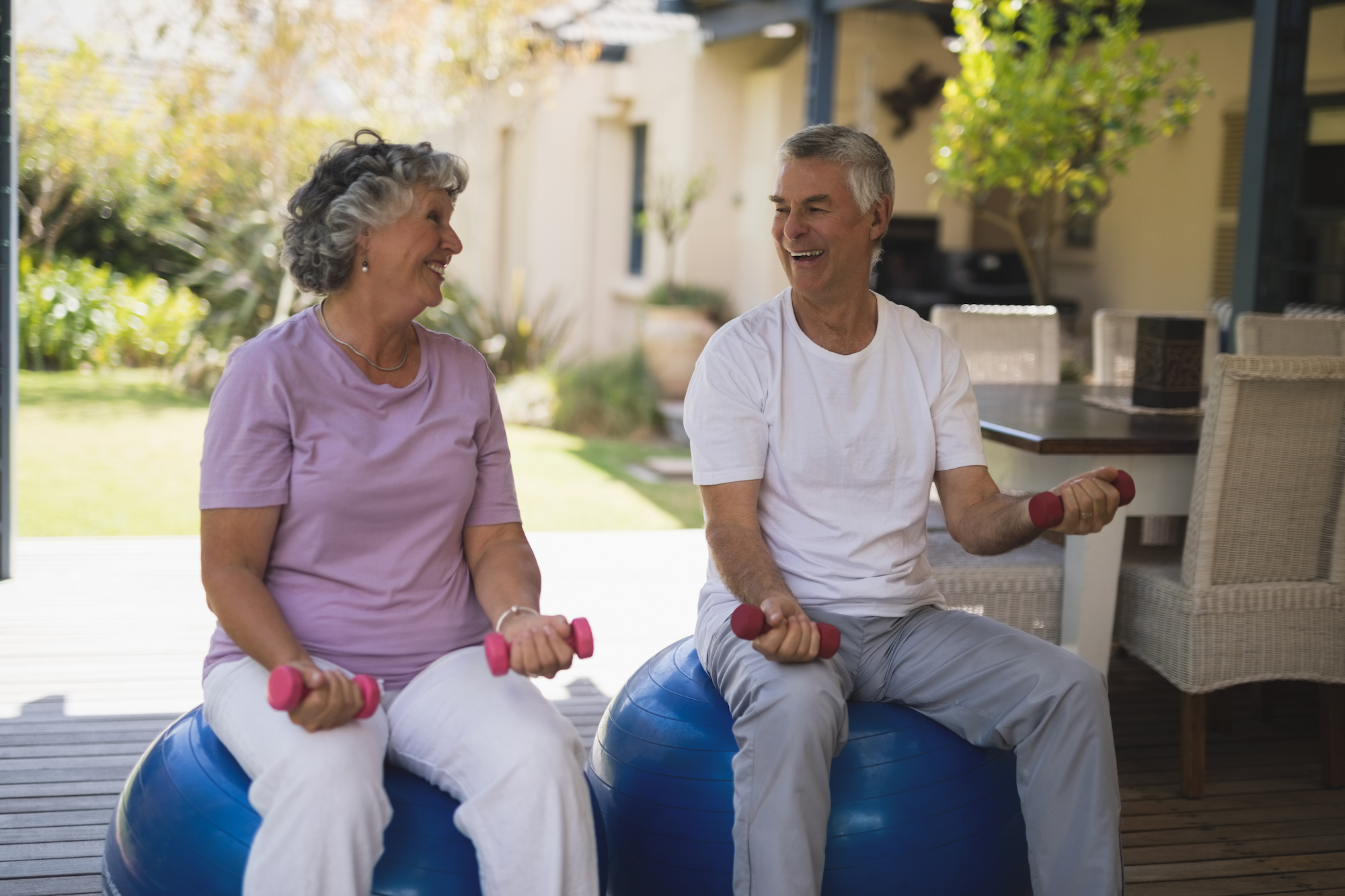 two seniors on balance balls with dumbells doing exercises in the back yard