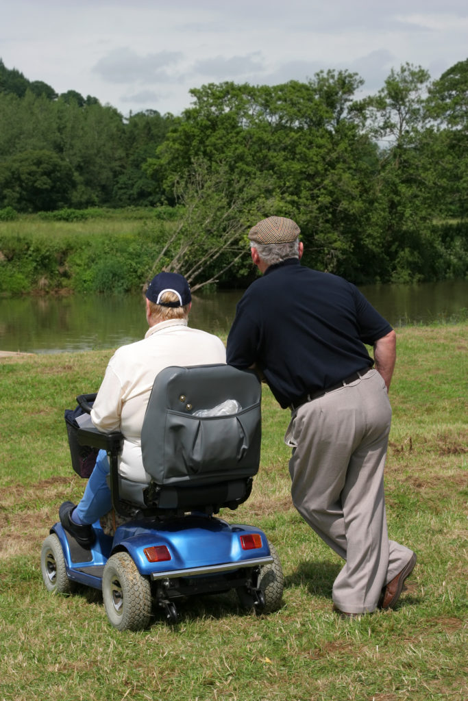 two seniors with one in a mobility scooter looking at calm river in the park