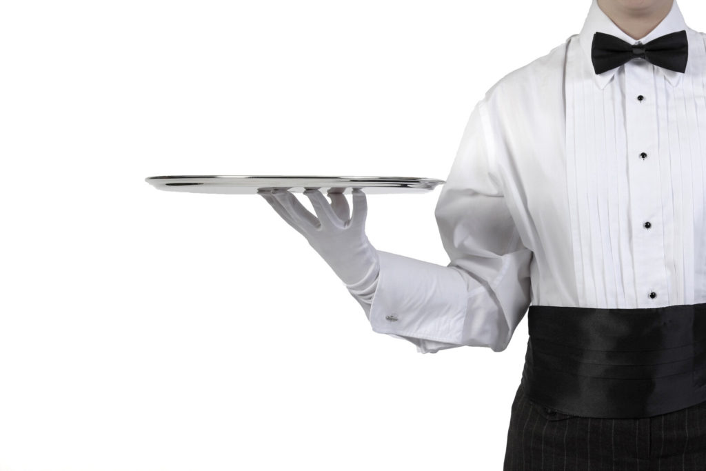 A waiter in a tuxedo holds a silver tray.