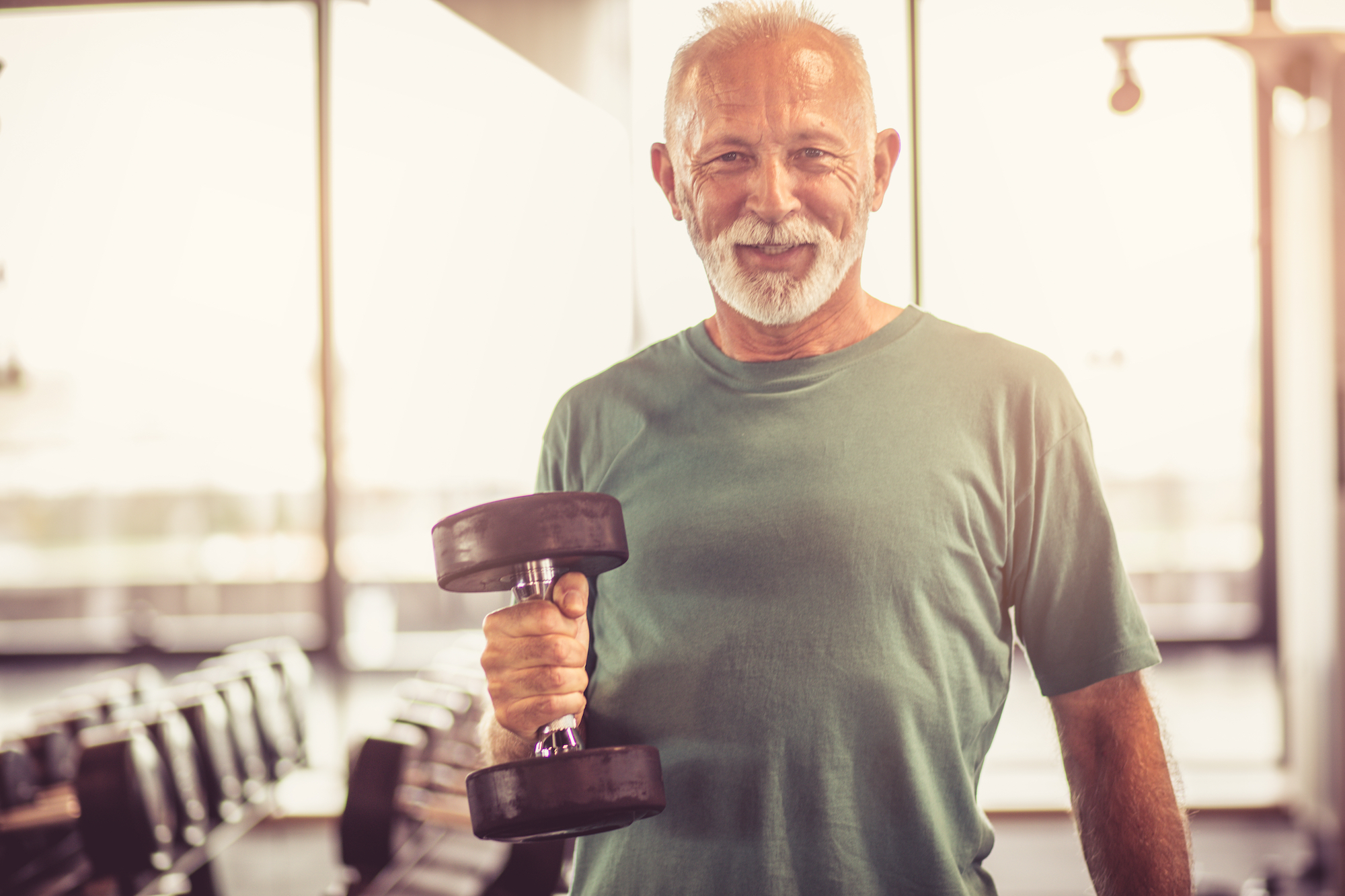 white haired man with beard lifing a dumbell at a gym