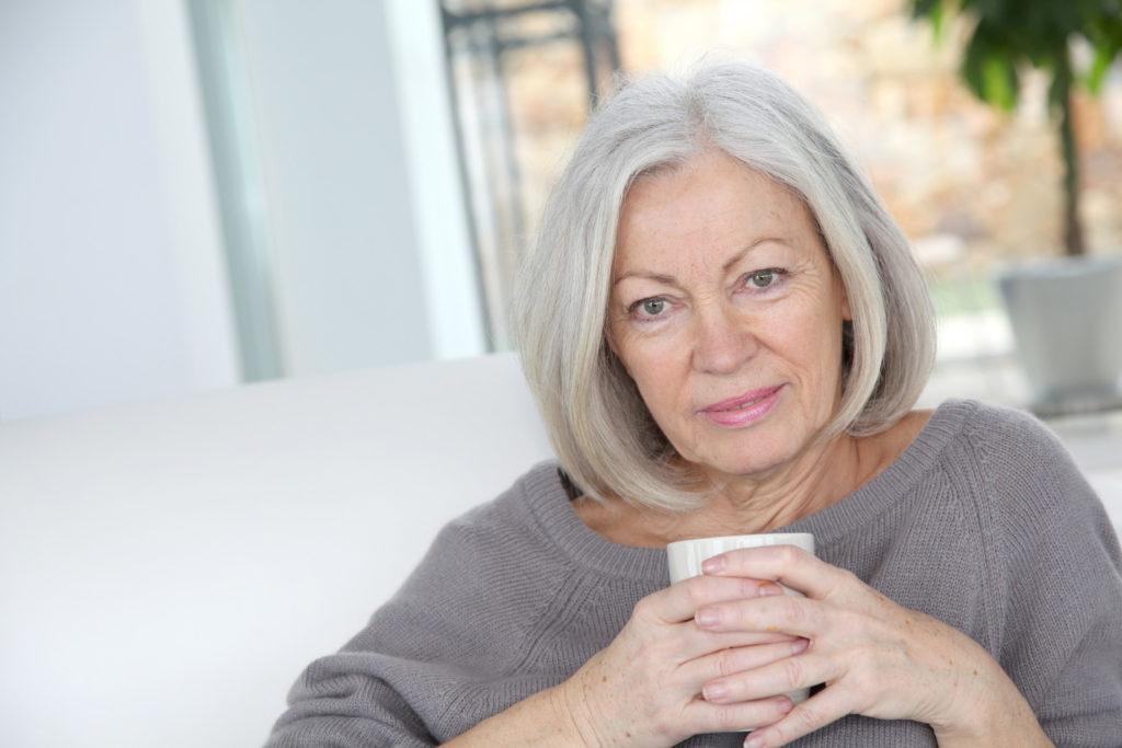 A senior woman holds a mug full of coffee.