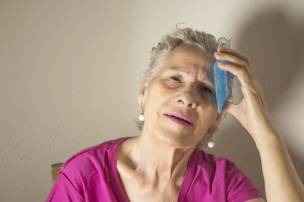 A senior woman uses a cold compress on her forehead to relieve a headache