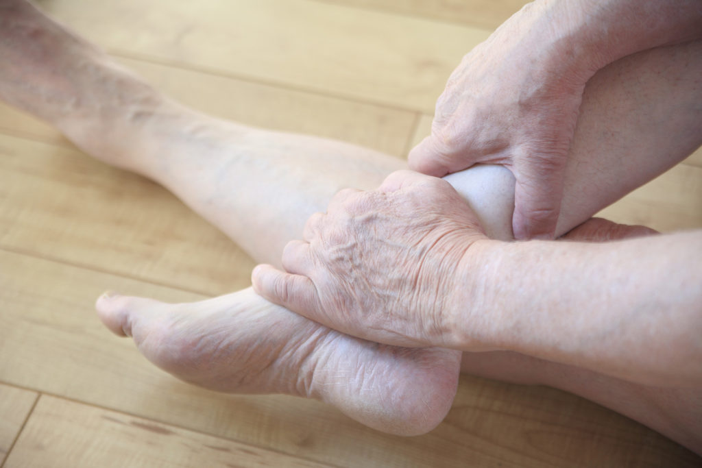A senior man holds his ankle and feet.