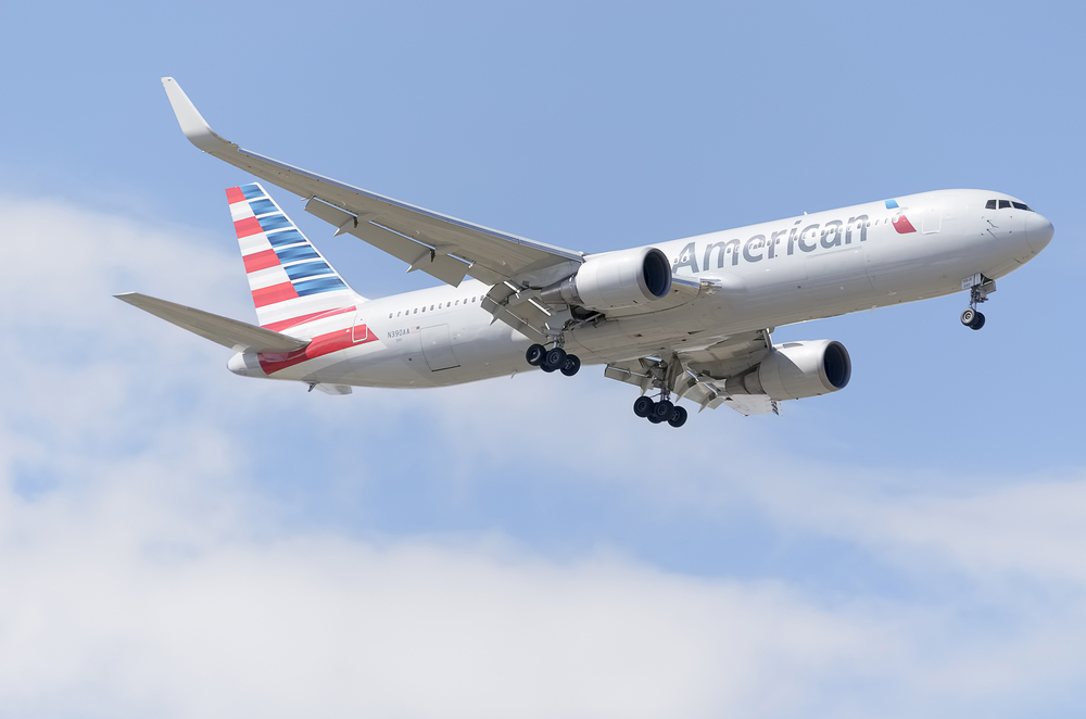 American Airlines Group plane flying in a blue sky with clouds