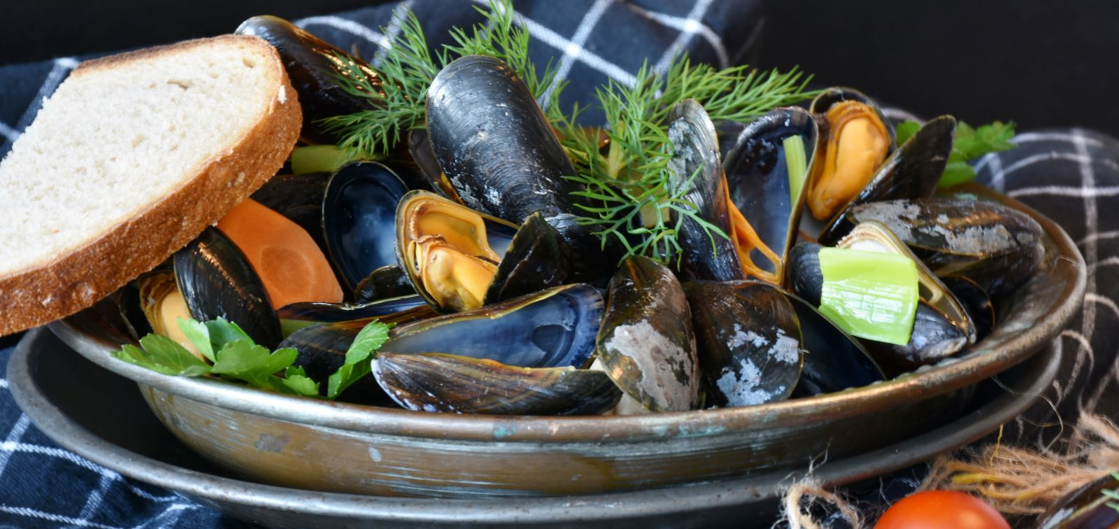 Mussels and vegetables in a clay bowl with dill and cilantro garnish and piece of bread set on the edge of the bowl