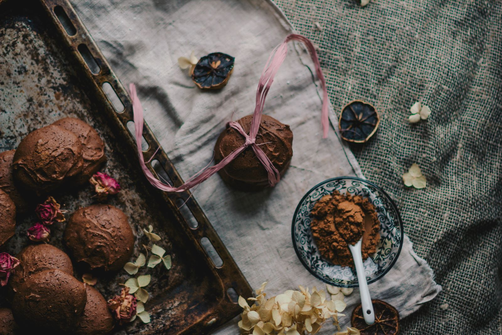 Dark cloth background with a lighter strip of cloth laying on top with dark chocolate powder and a dark chocolate cookies with a bow wrapped around. in the left side a baking sheet with more dark chocolate cookies and flower petals scattered between them