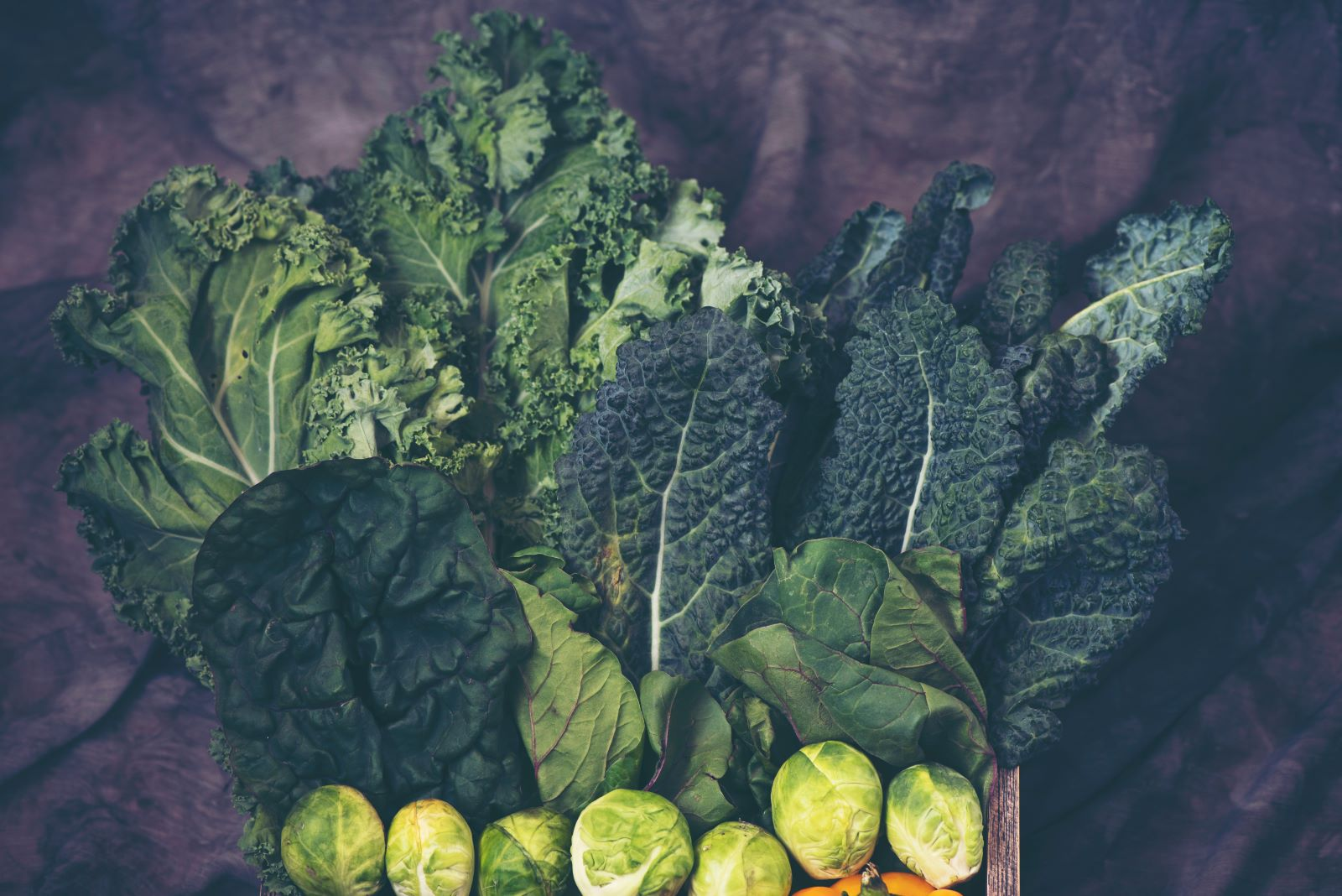 Crate with a variety of greens like kale, collards, and Brussels sprouts sitting on a dark drop cloth