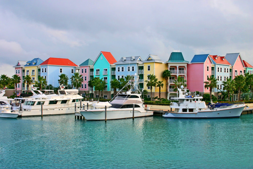 Grand Cayman houses sit next to boats in the water.