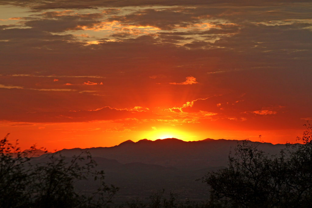 Sunrise over Green Valley with mountains on the horizon and an orange sky