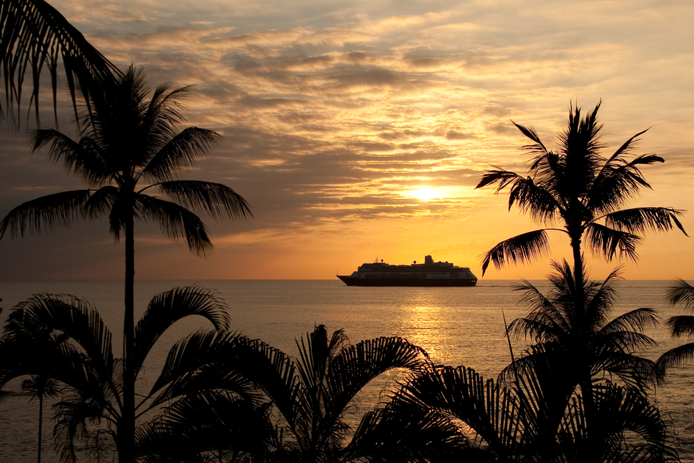 A Hawaiian sunrise over the ocean with palm trees and a cruise ship