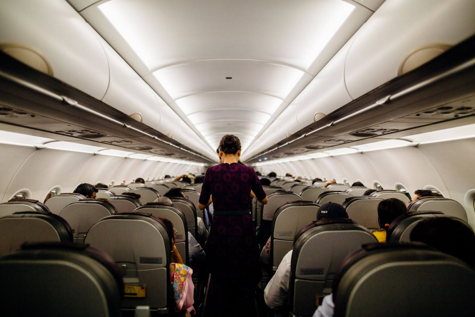 5 Airline Discounts for Seniors -The inside of a full commercial passenger plane with a flight attendant standing in the aisle