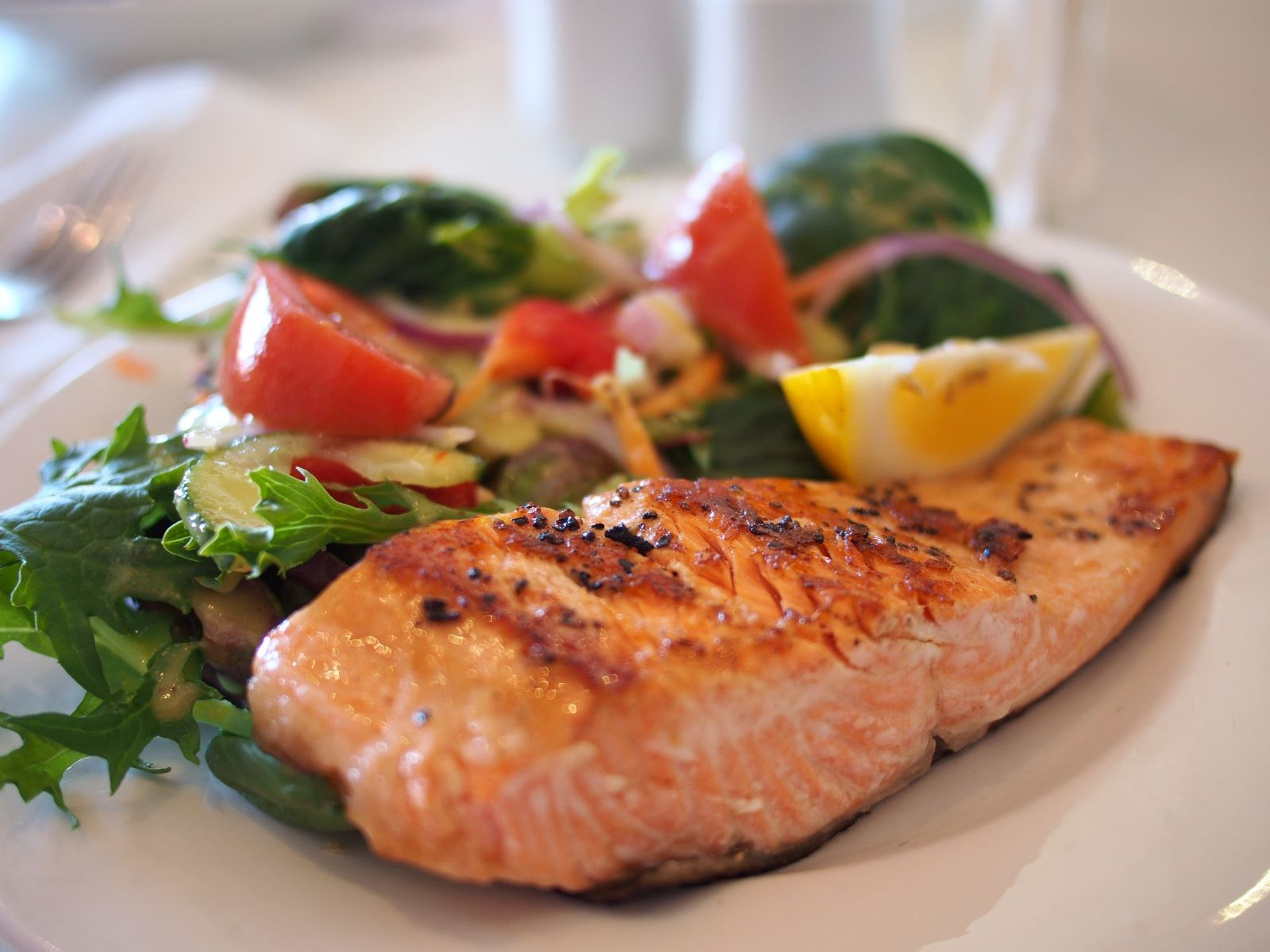 Spring green salad with tomatoes and a salmon steak with a wedge of lemon
