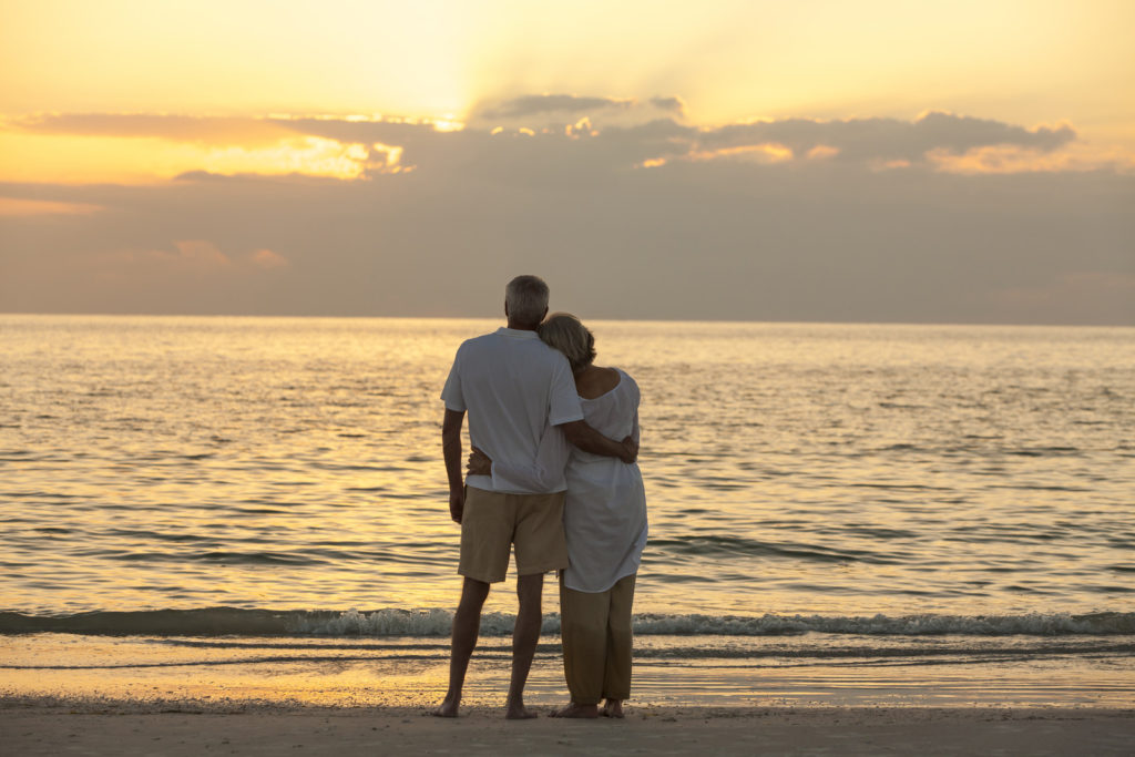 A couple watches the sun set on the water while standing on the beach.