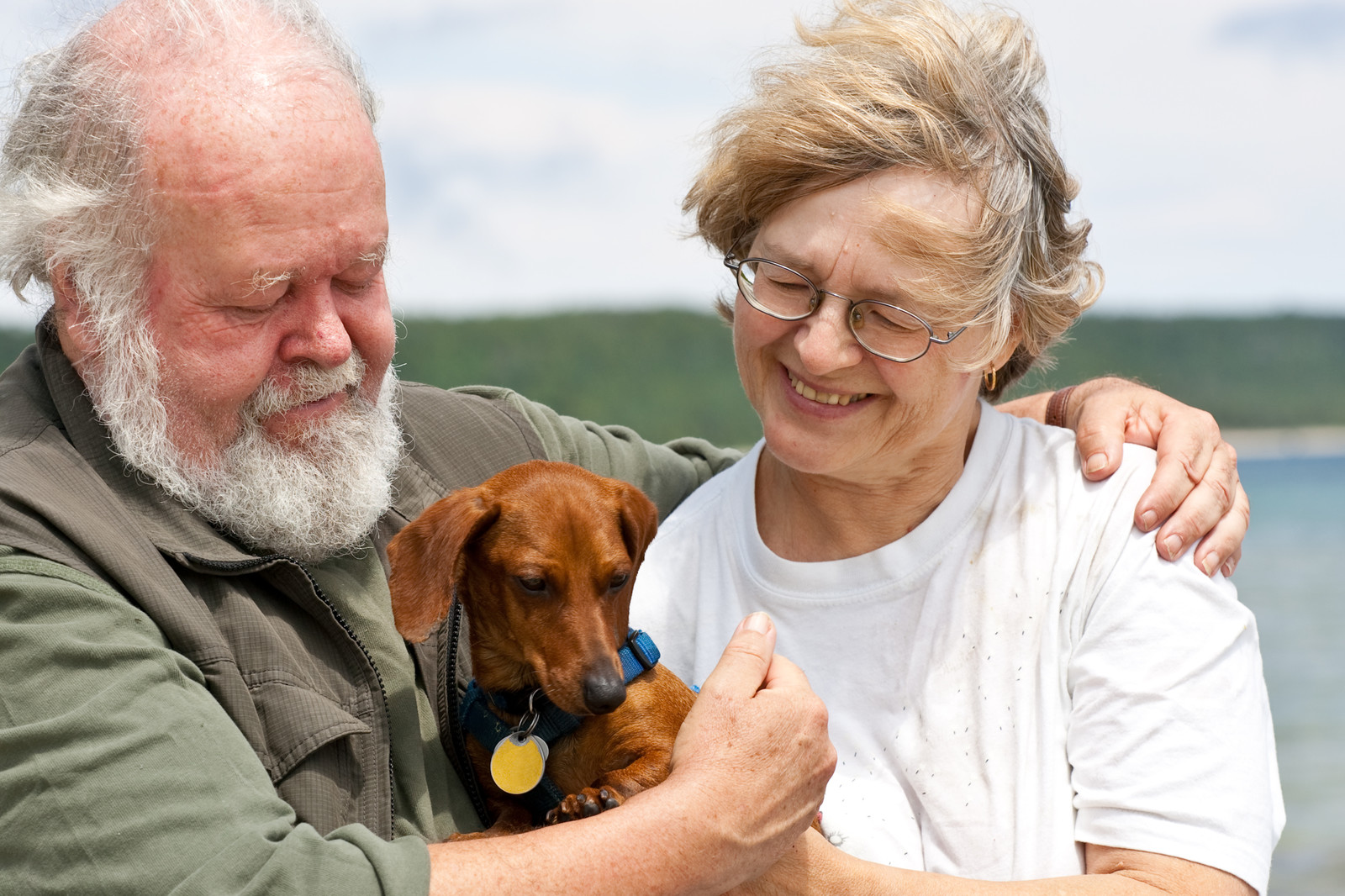 A smiling couple on a windy day holding a reddish brown dachshund, with a lake in the background.