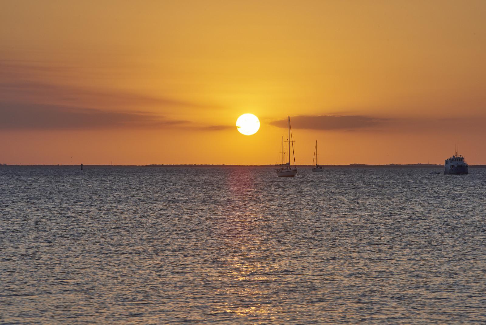 Golden Sunset over Punta Gorda coastal area with three boats floating on the horizon