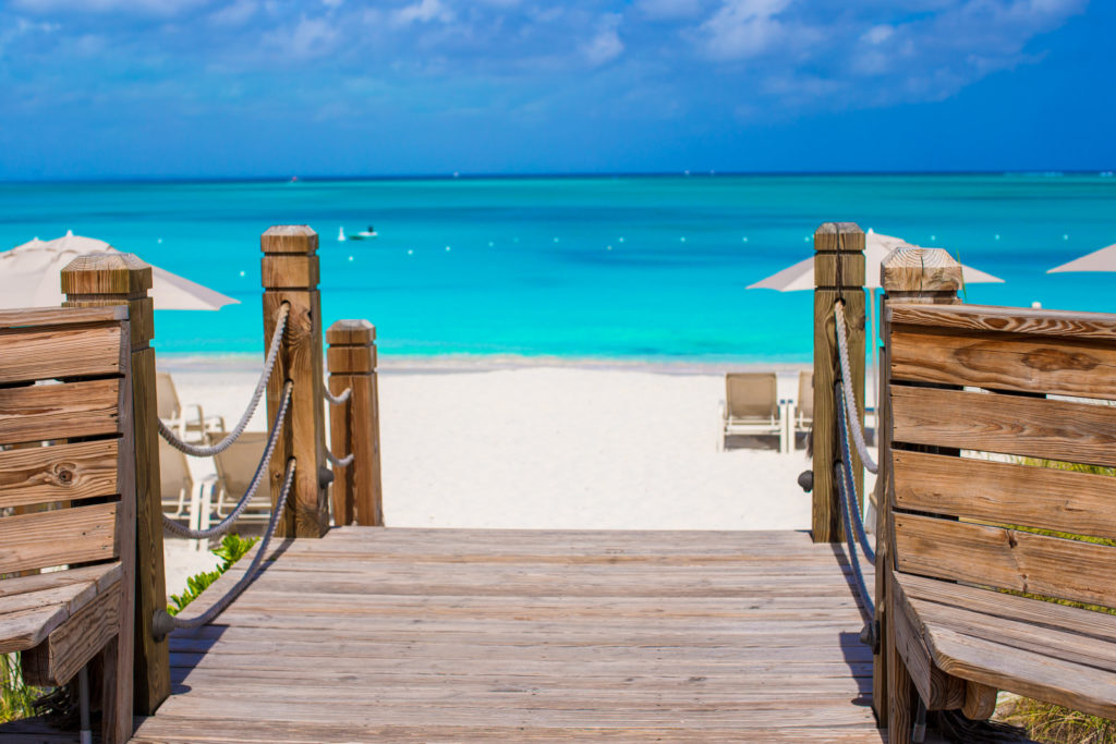 A beautiful bridge that leads to bright turquoise waters on the beach.