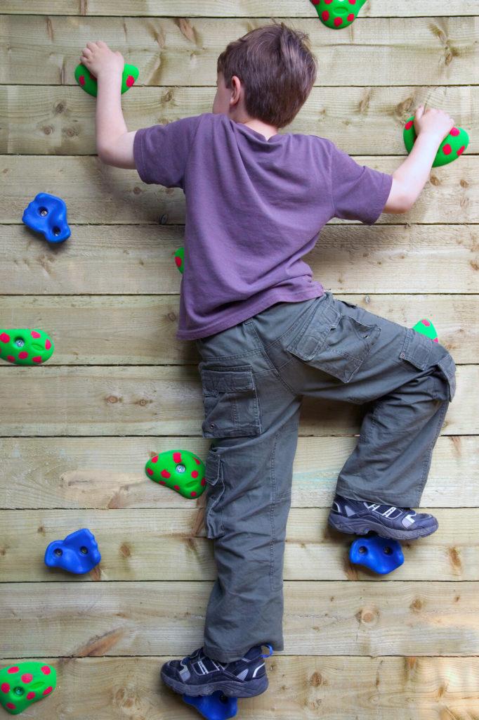 A child climbs a rock climbing wall.