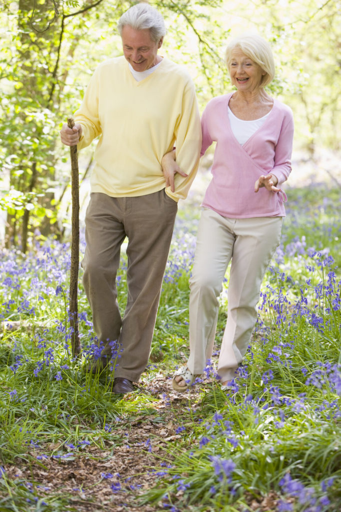 A senior man and woman take a walk outside together.