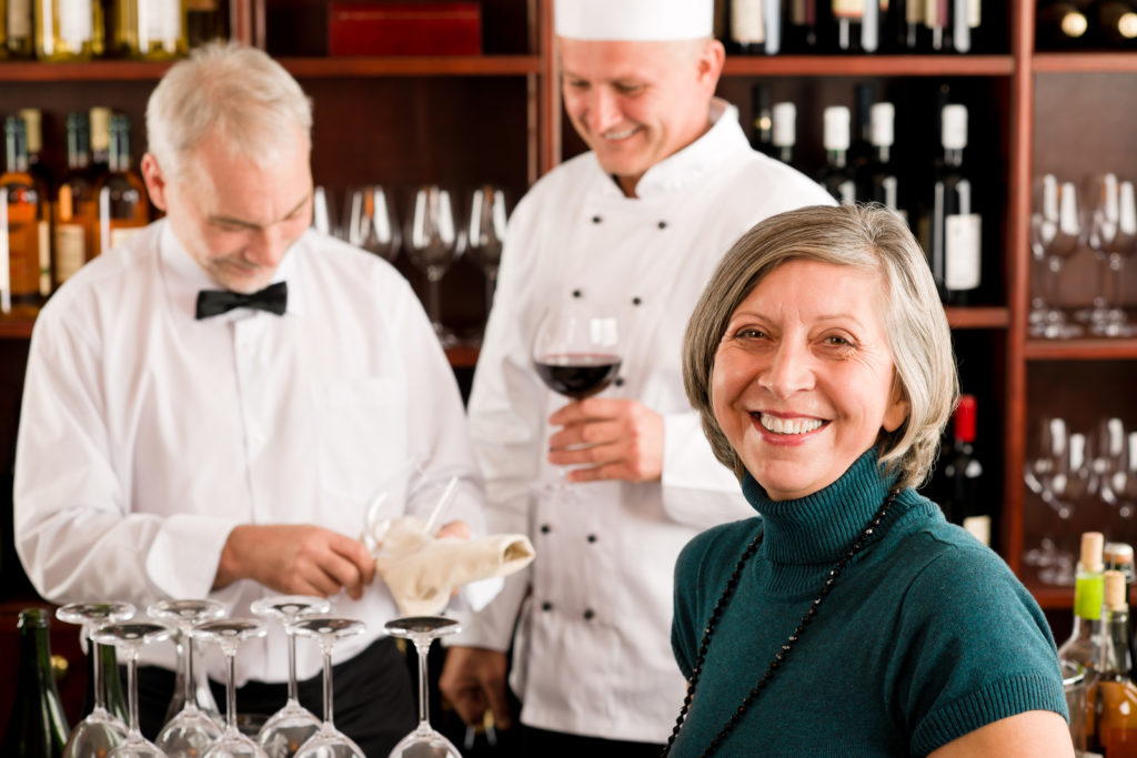 A senior woman sits at a wine bar with two chefs