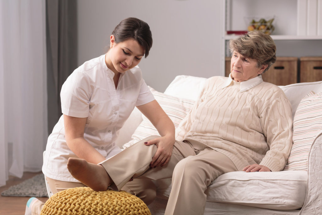 A woman elevates her knee with the help of a caregiver.
