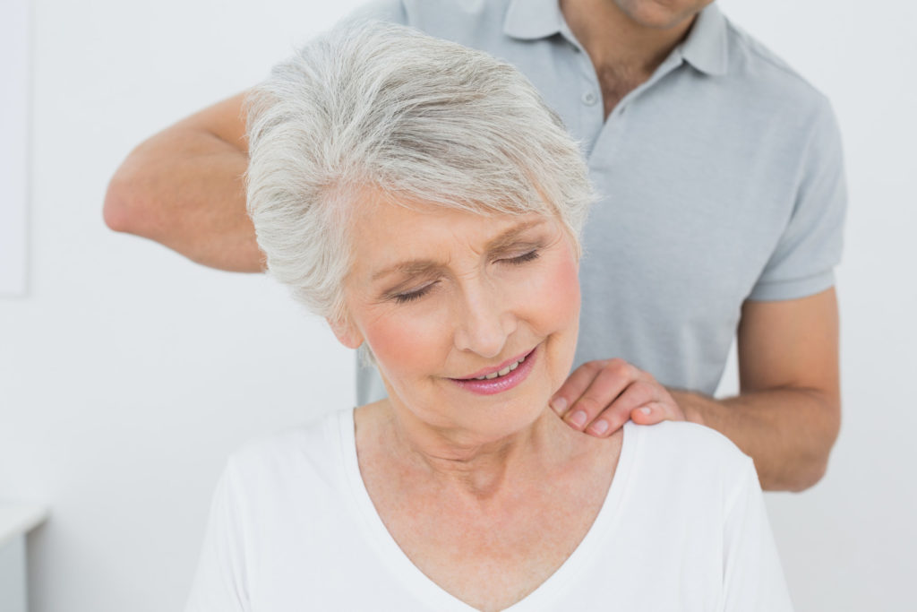 A woman gets a neck massage from a therapist.