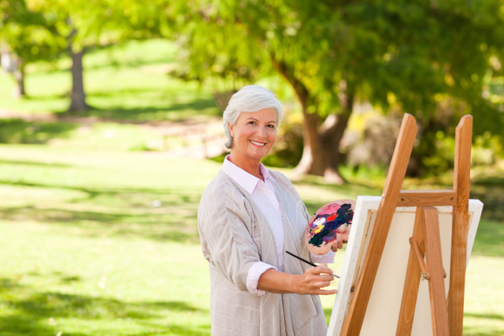 A senior woman with paints and an easel is painting in a sunny park.