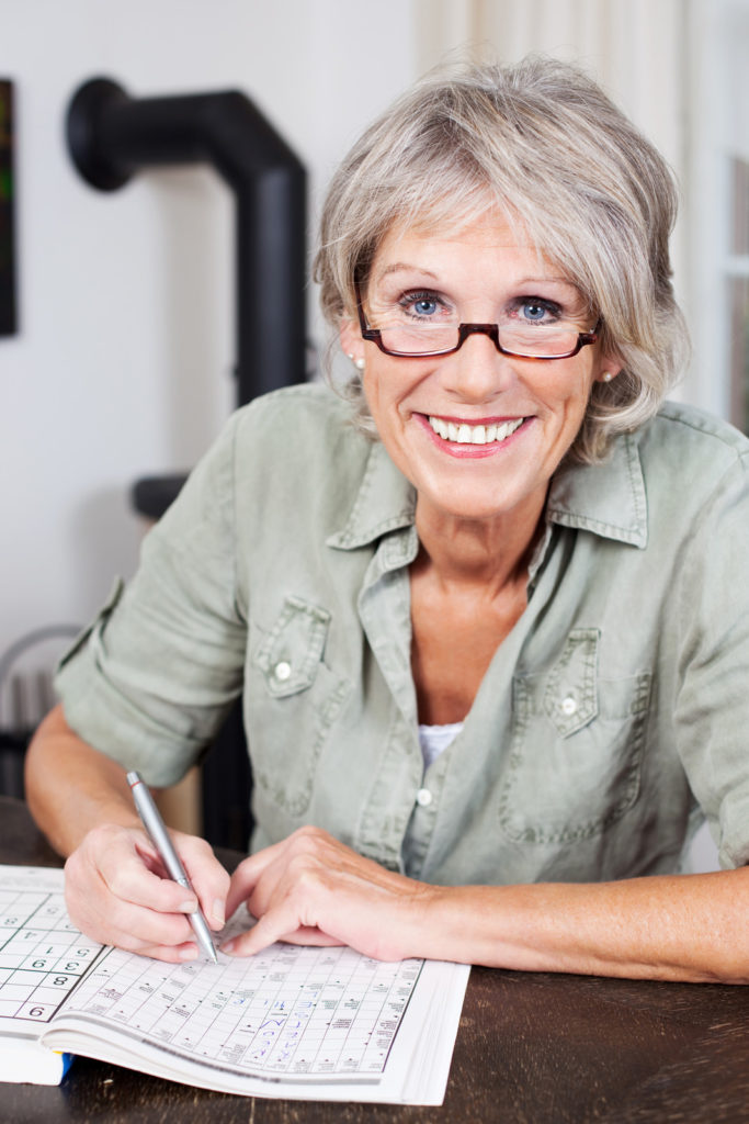 A woman wearing glasses does a crossword puzzle.