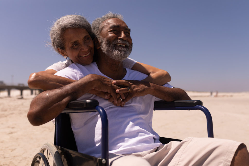 A man in a wheelchair sits on the beach as his wife puts her arms around him.