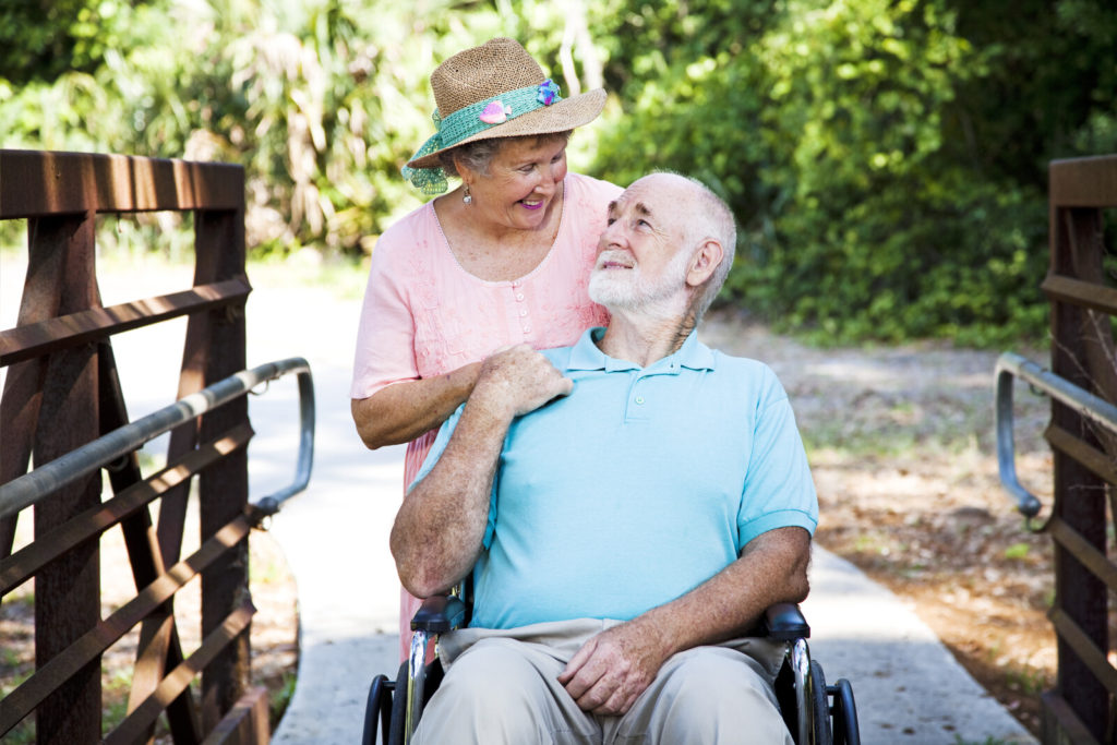 A man in a wheelchair is accompanied by his wife outdoors in a beautiful environment.
