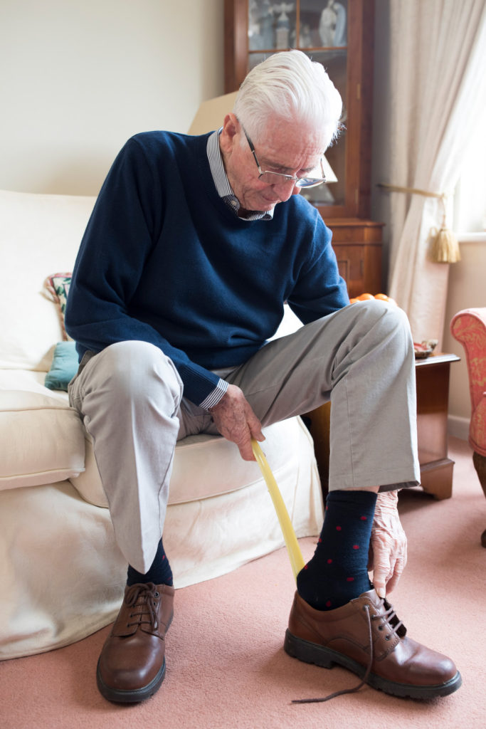 A senior man uses a shoehorn to put on shoes.