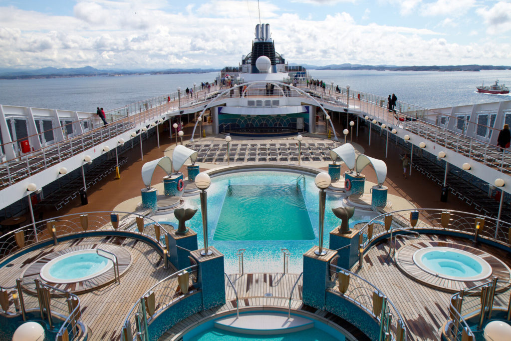 A cruise ship from the top, with a pool and two hot tubs visible.