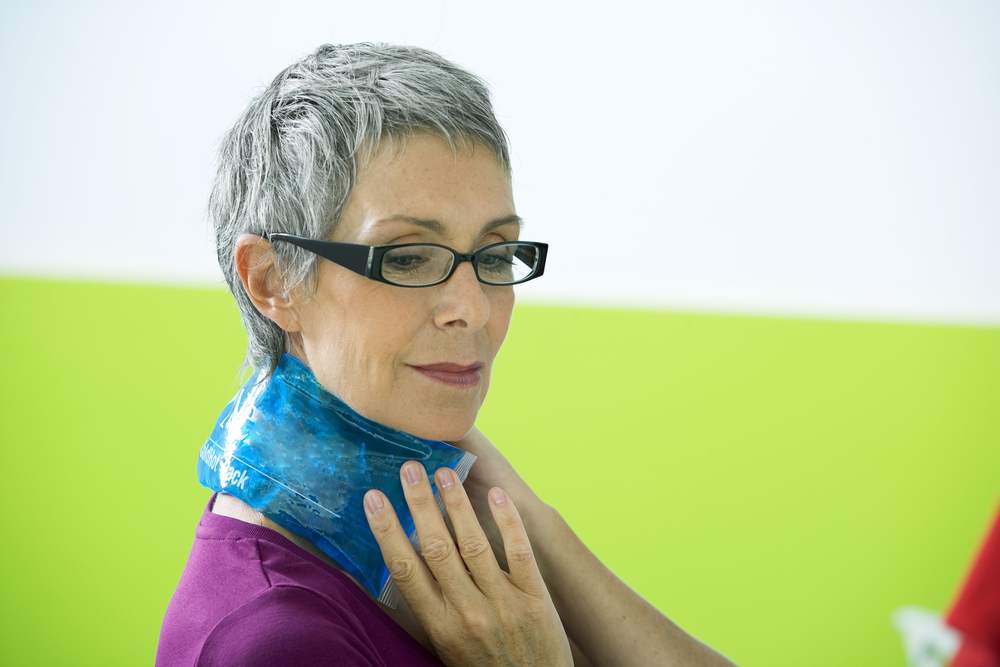 senior applying cold pack to neck for cold therapy