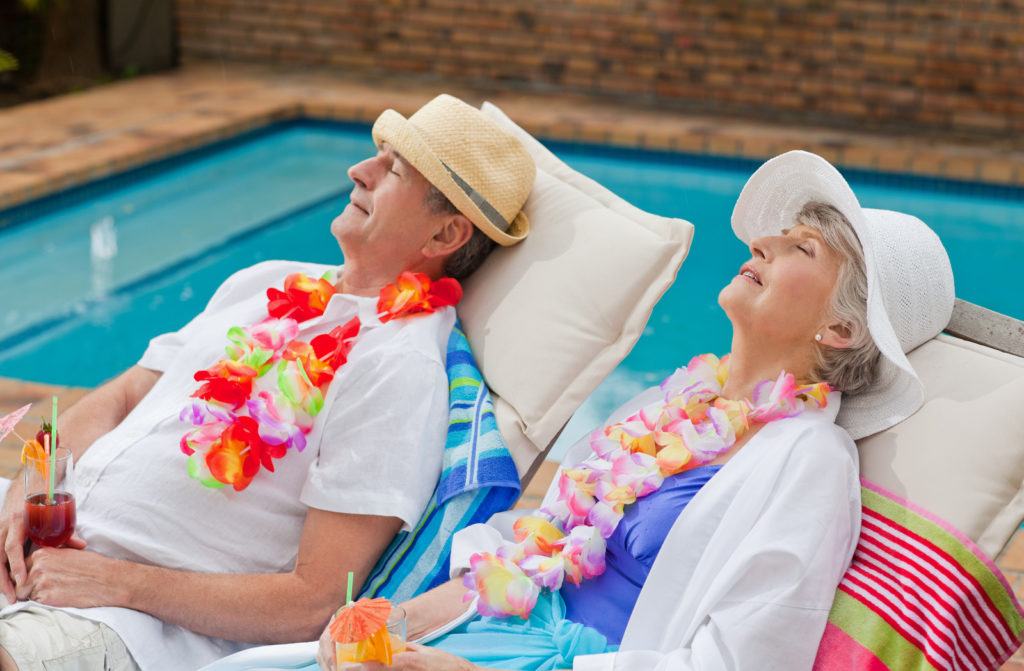 A senior couple on vacation lies next to a pool.