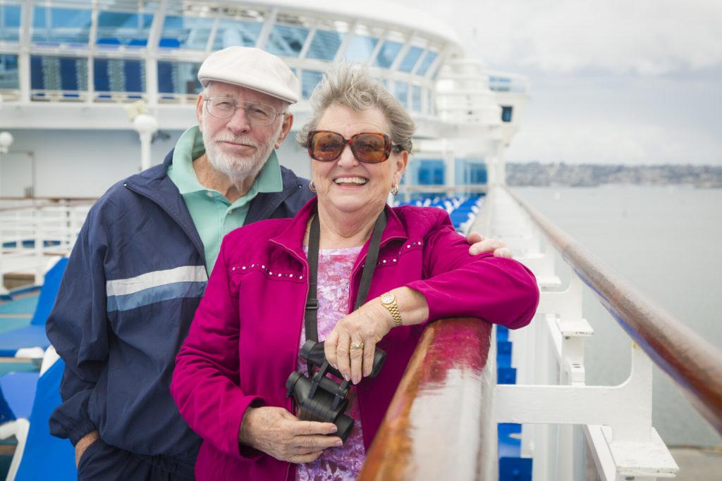 A senior couple is on a cruise ship deck.