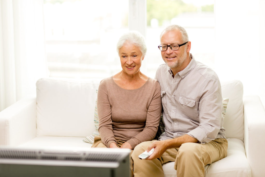 A senior couple watches TV