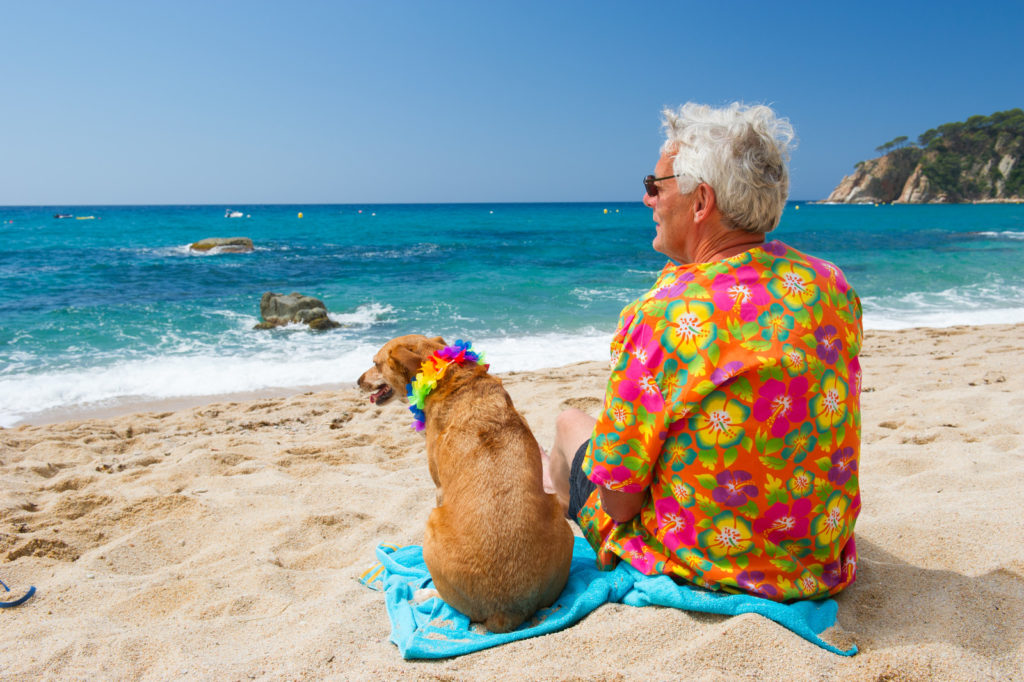 A senior man in a bright shirt sits on the beach with his dog.