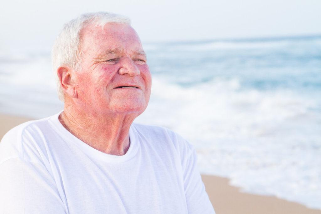 A senior man smiles in the sunlight on the beach.